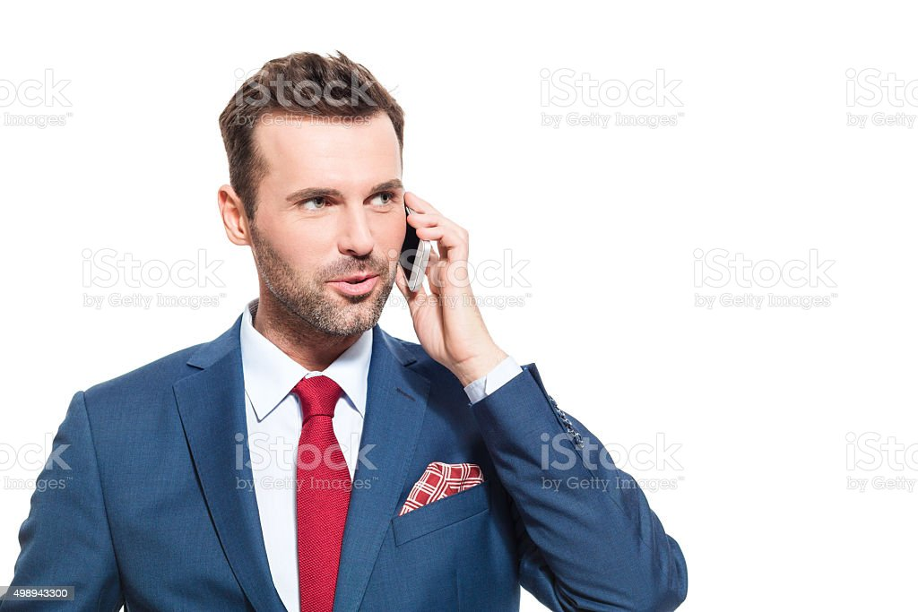 Confident businessman wearing suit talking on cell phone Portrait of elegant businessman wearing suit talking on mobile phone. Studio shot, one person, isolated on white. 2015 Stock Photo