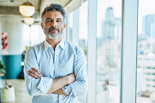 Portrait of confident mature businessman. Male entrepreneur is standing with arms crossed. He is at coworking office.