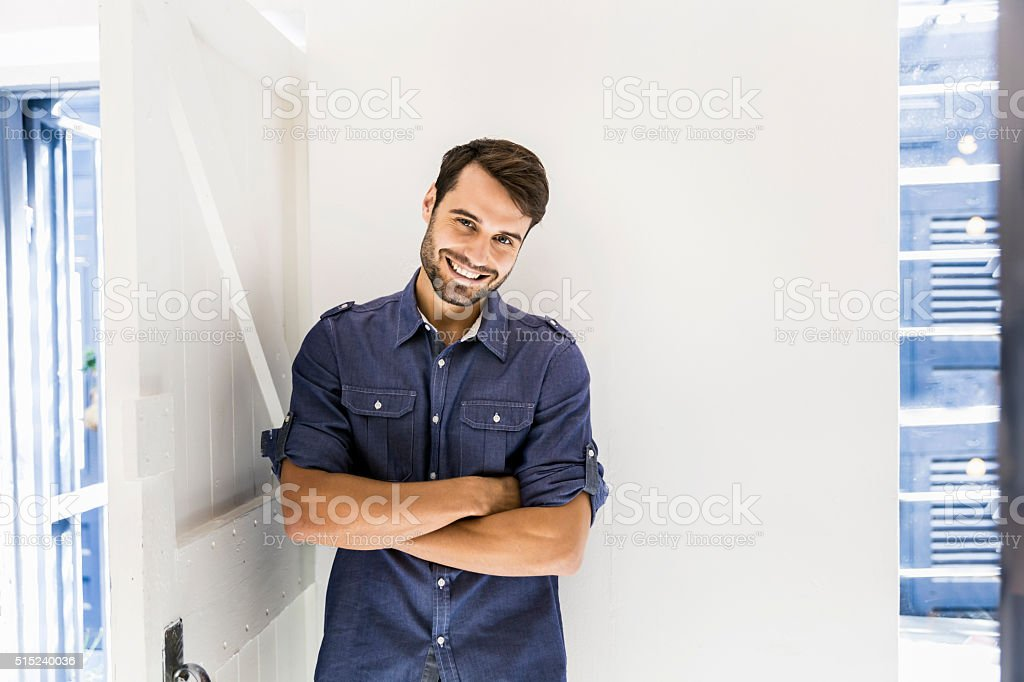 Confident businessman with arms crossed smiling in office stock photo