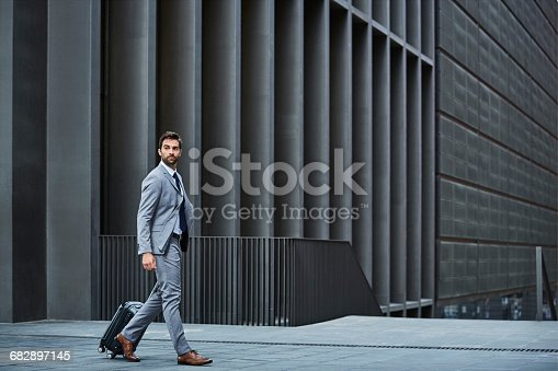istock Confident businessman with bag against building 682897145