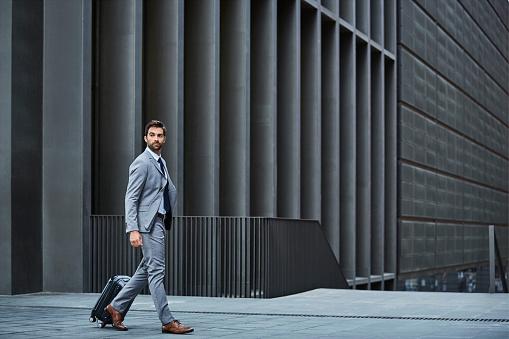 Confident businessman with bag against building