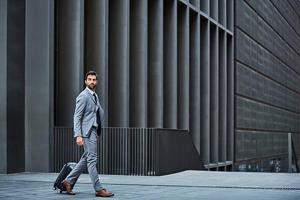 confident businessman with bag against building - 男性のファッション ストックフォトと画像