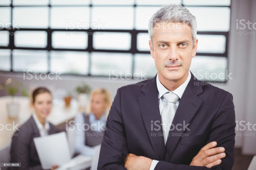Confident businessman with colleagues in background royalty-free stock photo