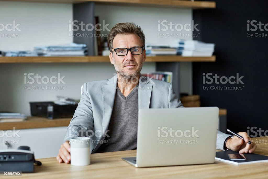 Confident businessman with laptop at desk stock photo