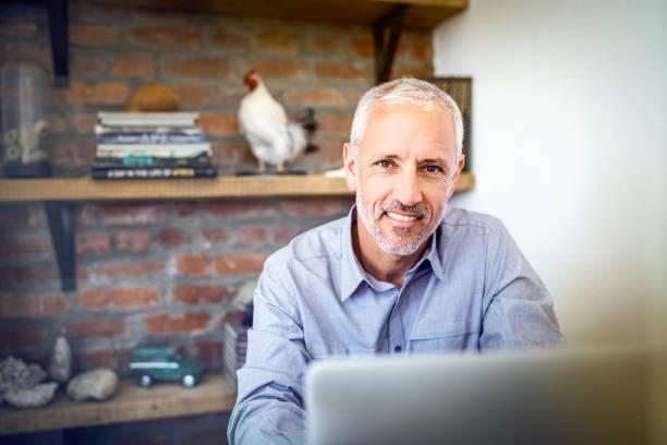 Selbstbewuster Geschäftsmann mit Laptop im Büro – Foto