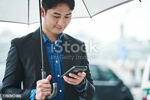 Confident handsome businessman with umbrella using mobile phone. Male professional is standing in city on rainy day. He is on business trip in Taiwan.