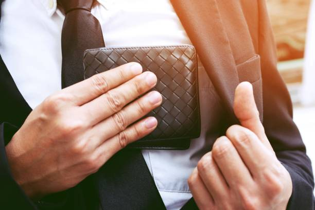 confident businessman young posing in save keeping your wallet in the suit pocket inside of his. - wallet stock pictures, royalty-free photos & images