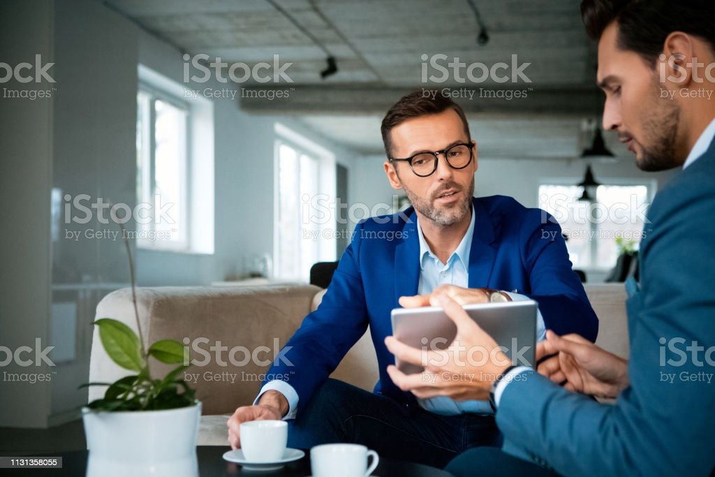 Confident businessmen discussing at office Confident male entrepreneurs planning strategy while sitting at workplace. Businessmen are discussing over digital tablet during meeting. They are working at creative office. 30-39 Years Stock Photo