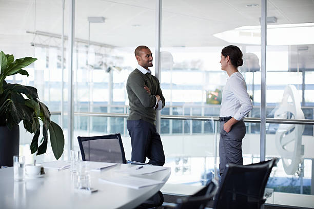 Confident businesspeople discussing Confident businesspeople discussing in conference room at office distant stock pictures, royalty-free photos & images