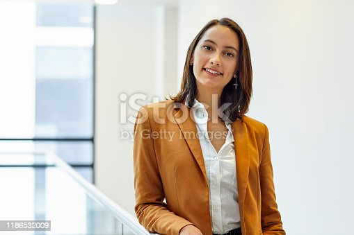 Portrait of confident businesswoman in office. Female entrepreneur is wearing brown blazer. She is at coworking space.