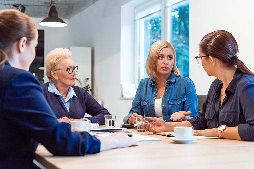 Confident Businesswoman Discussing With Colleagues Stock Photo - Download Image Now