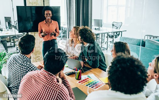 842214506 istock photo Confident businesswoman discussing with colleagues. 1214358349