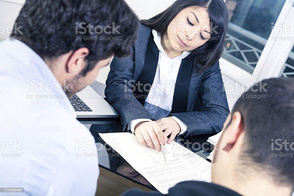 Confident businesswoman explaining to customers stock photo