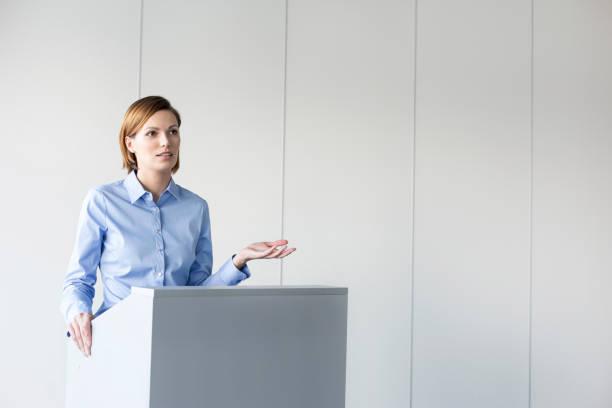 Mujer de negocios confiada dando discurso en el podio contra la pared en la oficina - foto de stock