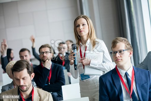 istock Confident businesswoman holding microphone while asking questions during seminar 616018388