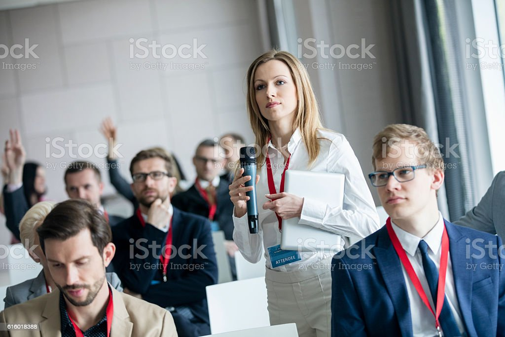 Confident businesswoman holding microphone while asking questions during seminar - foto de acervo