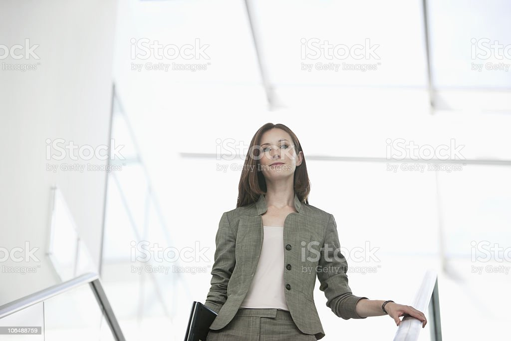 Confident businesswoman holding with laptop on staircase at office royalty-free stock photo