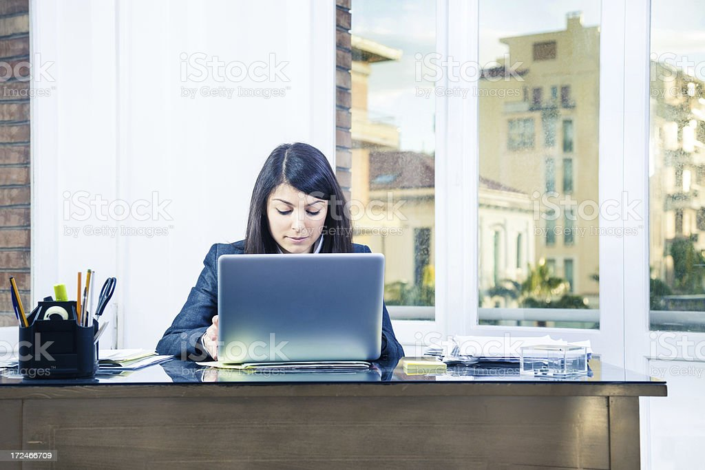 Confident businesswoman in her office working on laptop royalty-free stock photo