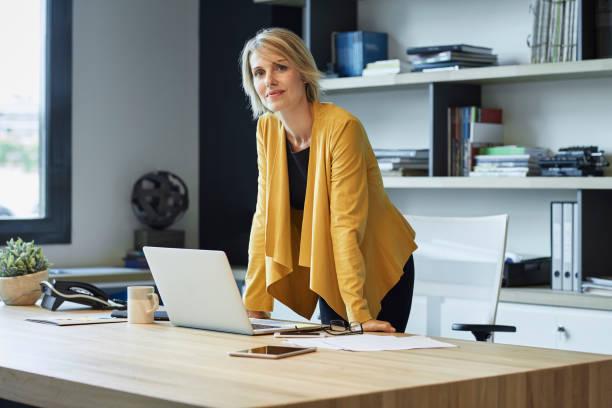 mulher de negócios confiante, apoiando-se na mesa - 35 39 anos - fotografias e filmes do acervo