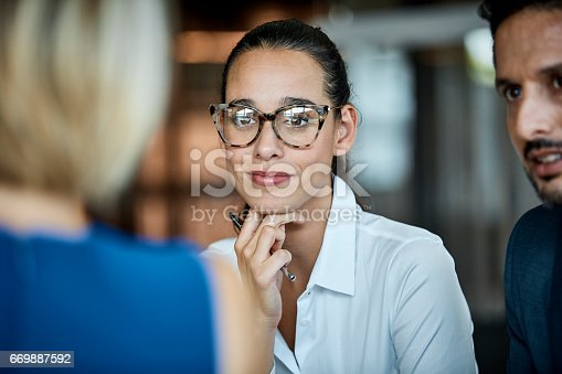 Confident businesswoman looking at female colleague. Professionals are sitting in textile factory. Male and female executives are working together.