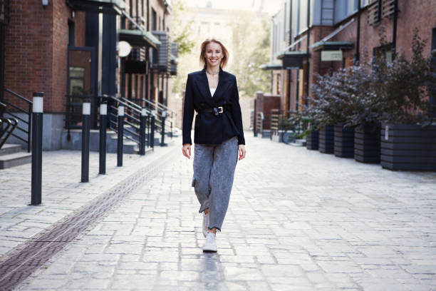 confident businesswoman or fashion blogger in stylish office clothes walking city street. . beautiful smiling woman going to work, wearing fashionable spring or fall black jacket, oversize slouchy jeans - spring fashion stock pictures, royalty-free photos & images