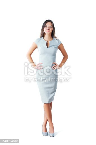 Full length portrait of confident businesswoman with hands on hips standing over white background. Vertical shot.