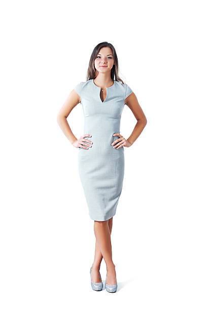 confident businesswoman Full length portrait of confident businesswoman with hands on hips standing over white background. Vertical shot. akimbo stock pictures, royalty-free photos & images