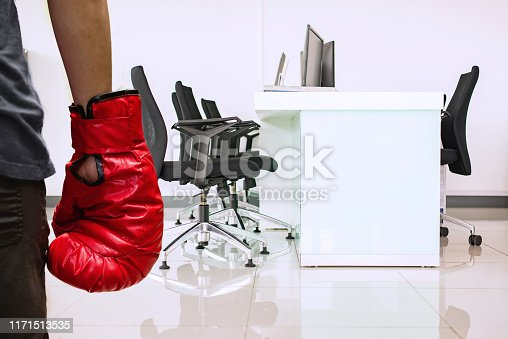 istock Confident businesswoman punching with boxing gloves in the meeting room in office, Leader with boxing gloves at conference table. 1171513535