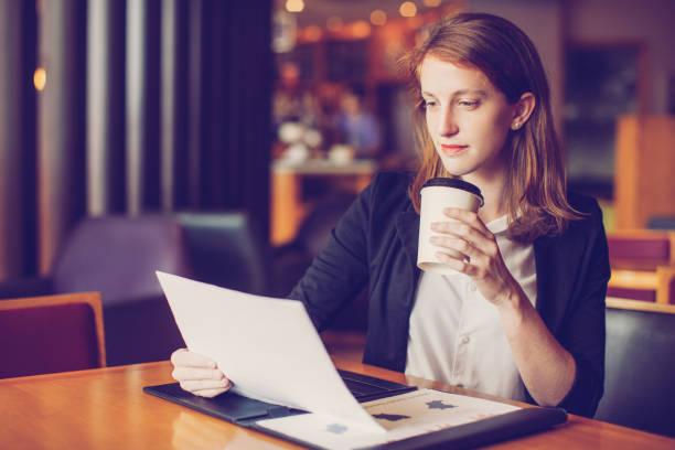 zuversichtlich, geschäftsfrau, die zeitung im café lesen - lesen arbeitsblätter stock-fotos und bilder