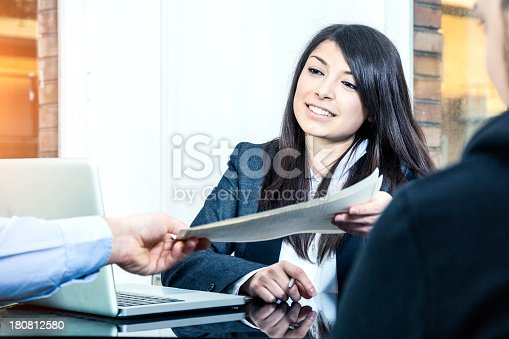istock Confident businesswoman showing contracts 180812580