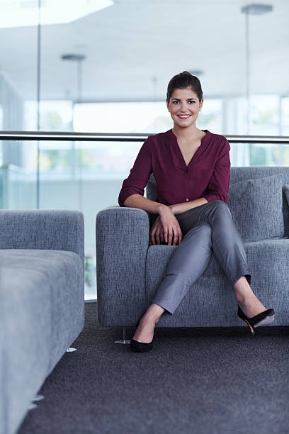 Confident businesswoman sitting on sofa Portrait of confident businesswoman sitting on sofa in office lobby cross legged stock pictures, royalty-free photos & images
