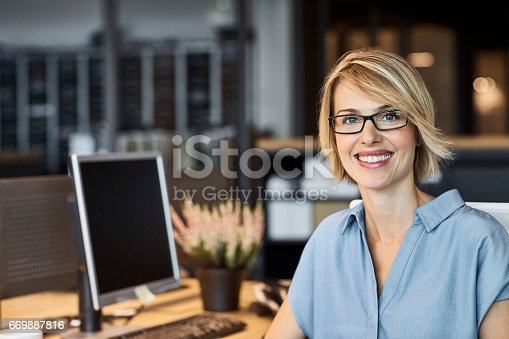 Portrait of confident businesswoman smiling in office. Female professional is with short blond hair. She is in textile factory.