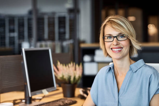 Confident businesswoman smiling in office Portrait of confident businesswoman smiling in office. Female professional is with short blond hair. She is in textile factory. one mid adult woman only stock pictures, royalty-free photos & images