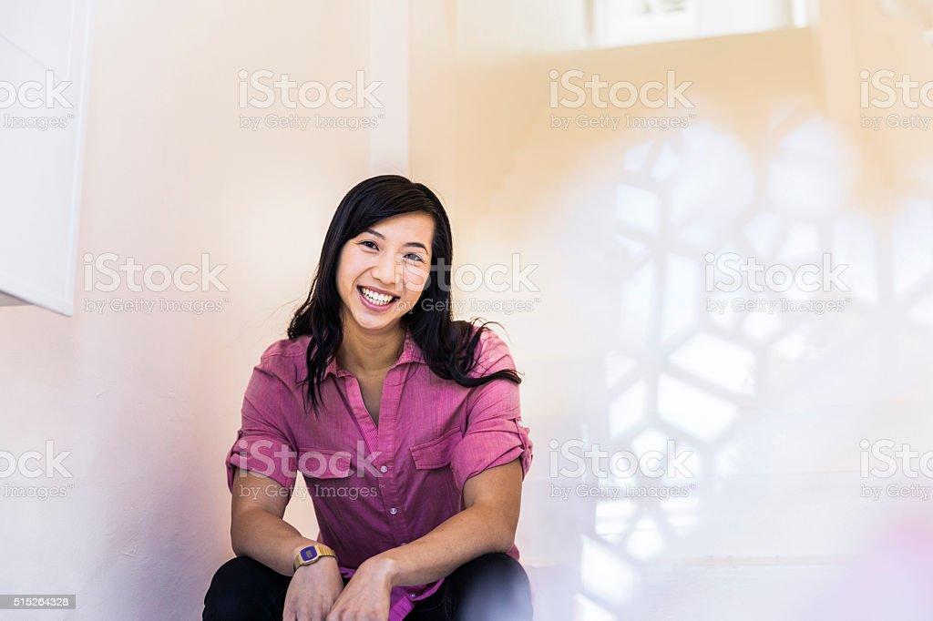 Pewnie Bizneswoman uśmiech, gdy siedzi w biurze. – zdjęcie