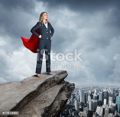 A very confident businesswoman stands with her hands on her hips on top of a rocky view point that looks over the New York City skyline.