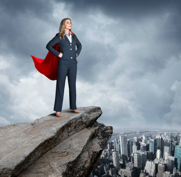 Confident Businesswoman Stands Ready To Take On World A very confident businesswoman stands with her hands on her hips on top of a rocky view point that looks over the New York City skyline. headland stock pictures, royalty-free photos & images