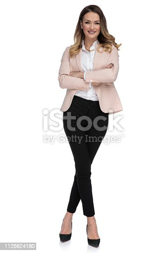 confident businesswoman stands with arms folded and legs crossed on white background, full body picture