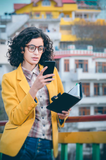 Confident businesswoman uses a smartphone and diary in hill city. stock photo