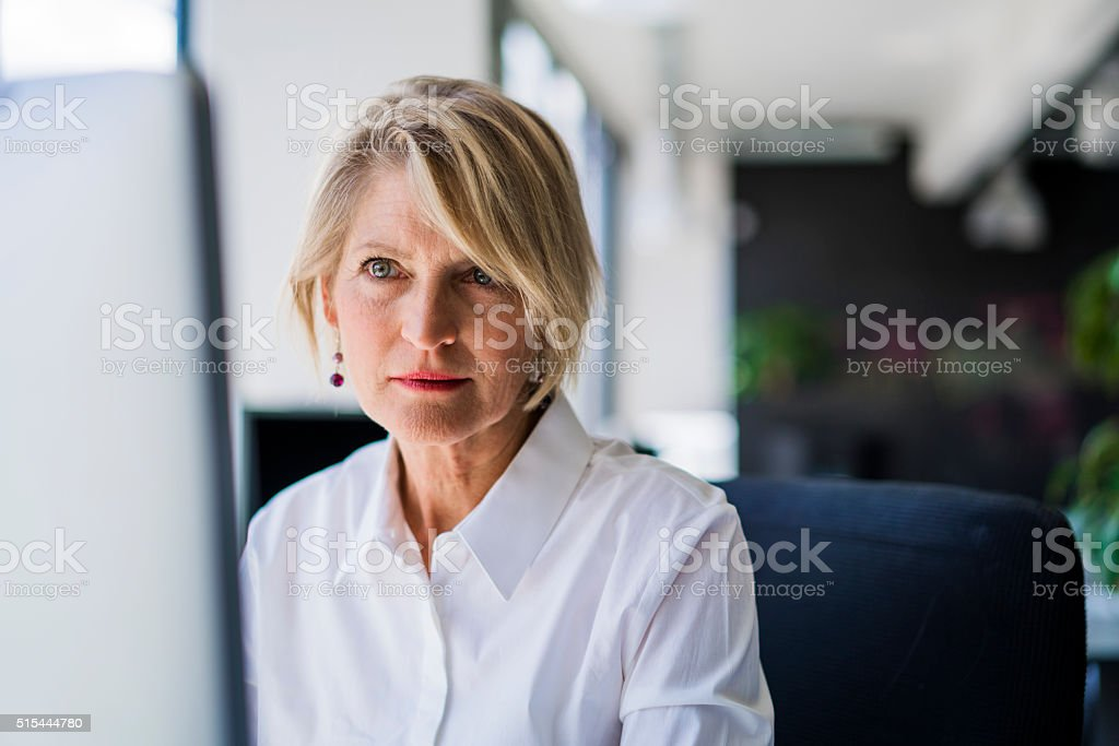 Confident businesswoman using computer stock photo