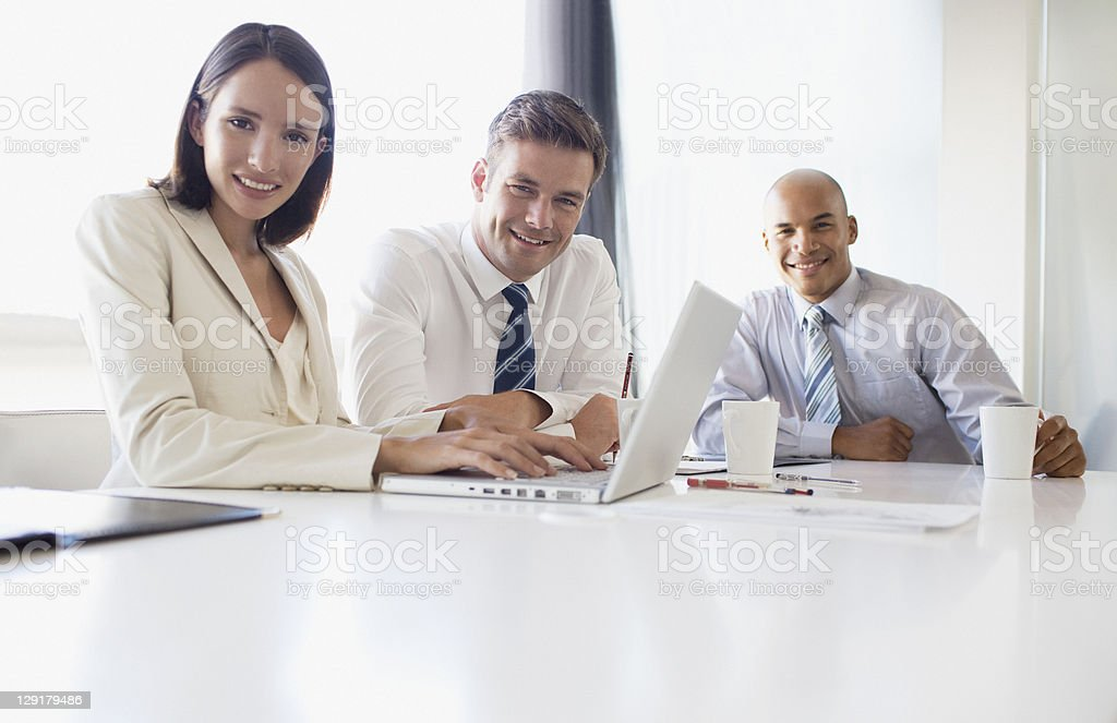 Confident businesswoman using laptop with colleague royalty-free stock photo