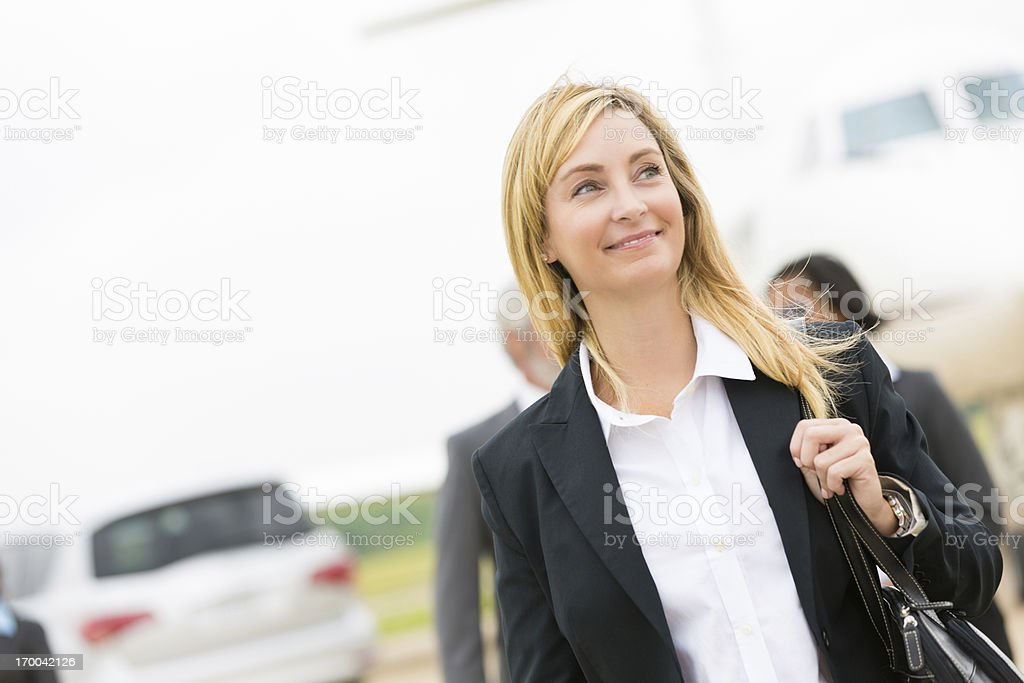 Confident businesswoman walking away from plane after landing. stock photo