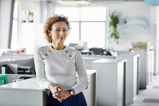 Portrait of confident mature female entrepreneur at workplace. Blond Professional is leaning on cabinet at office. Businesswoman is standing with hands clasped.