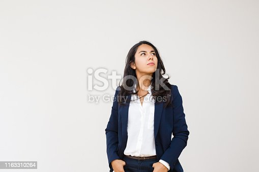 Confident businesswoman with hands in pockets looking up. Professional confident young businesswoman standing with hands in pockets isolated on grey background. Business concept