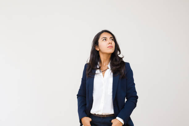 Selbstbewusste Geschäftsfrau mit Händen in Taschen, die nach oben schauen – Foto
