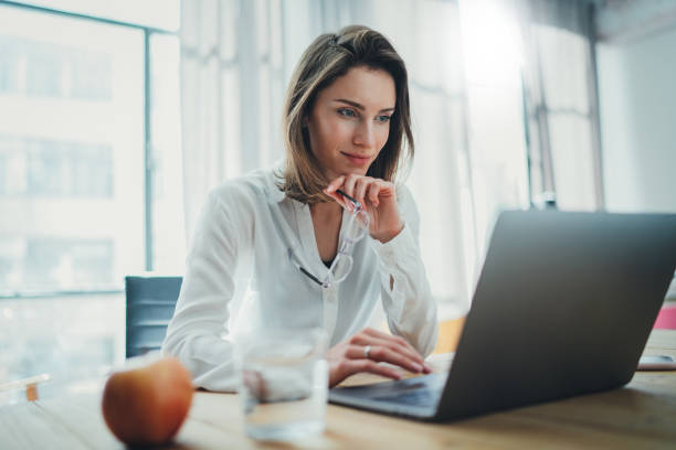 Confident businesswoman working on laptop at her workplace at modern office.Blurred background. Confident businesswoman working on laptop at her workplace at modern office.Blurred background business laptop stock pictures, royalty-free photos & images
