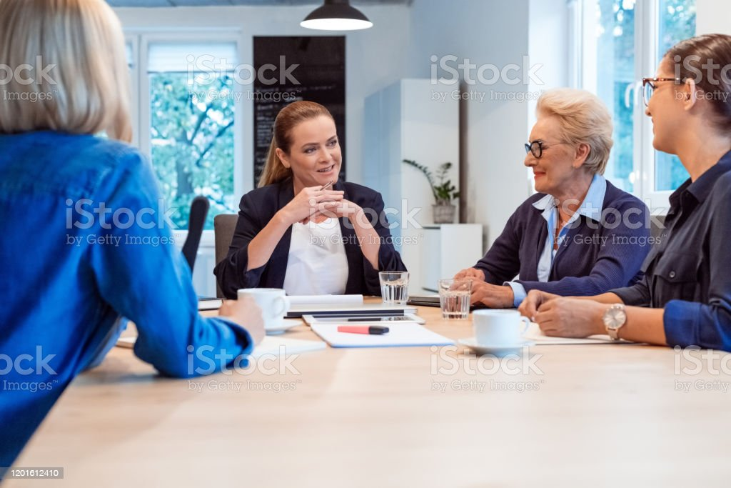 Confident businesswomen planning strategy at table Confident mature businesswoman discussing with colleagues. Female executives are running new business. They are sitting in board room at office. 35-39 Years Stock Photo