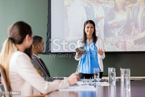 Businesswoman gestures as she explains an opportunity to for business people help out in the community. A photo in the background shows people volunteering in soup kitchen.