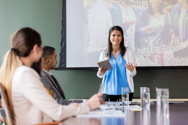 confident busineswwoman discusses charity event - organizzazione no profit foto e immagini stock