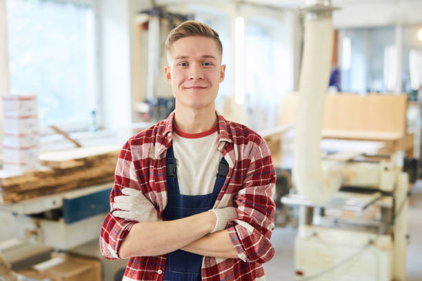 Confident carpentry student in work gloves stock photo
