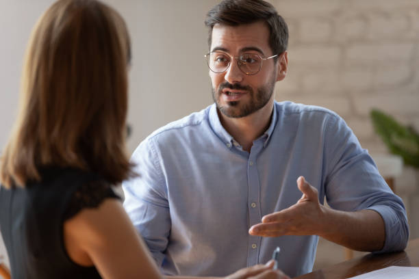 Confident caucasian male applicant answering on questions during job interview stock photo